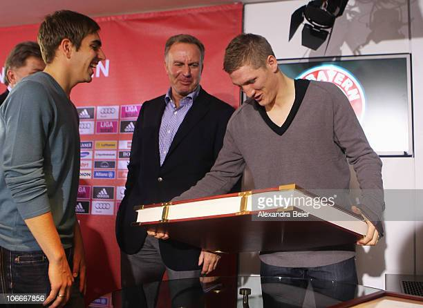 Bastian Schweinsteiger of Bayern Muenchen lifts up the club's chronicle as Philipp Lahm and CEO of Bayern Muenchen KarlHeinz Rummenigge watch him...
