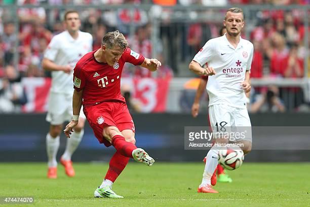 Bastian Schweinsteiger of Bayern Muenchen passes the ball as Daniel Brosinski of FSV Mainz 05 closes in during the Bundesliga match between FC Bayern...
