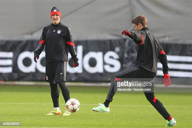 Bastian Schweinsteiger of Bayern Muenchen plays with his team mate Thomas Mueller during a Bayern Muenchen training session prior to their UEFA...