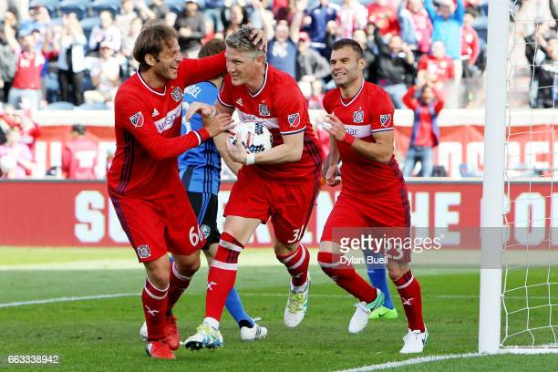 Bastian Schweinsteiger of Chicago Fire celebrates with Joao Meira and Nemanja Nikolic after scoring a goal in the first half against the Montreal...
