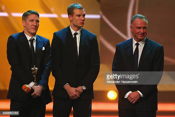 Bastian Schweinsteiger of FC Bayern Muenchen his team mate Holger Badstuber and CEO of Bayern Muenchen KarlHeinz Rummenigge receives the Team of the...