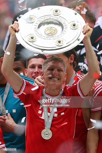 Bastian Schweinsteiger of FC Bayern Muenchen lifts the Bundesliga trophy following his team's match against Augsburg at the Allianz Arena on May 11...