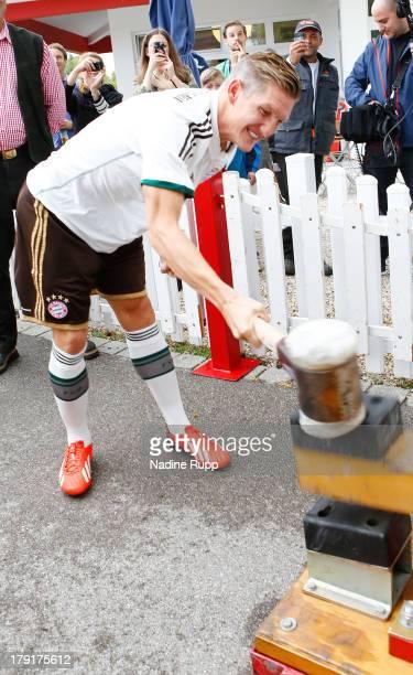 Bastian Schweinsteiger of FC Bayern Muenchen presents their new trikot in bavarian style while playing Oktoberfest games at Saebener Strasse training...