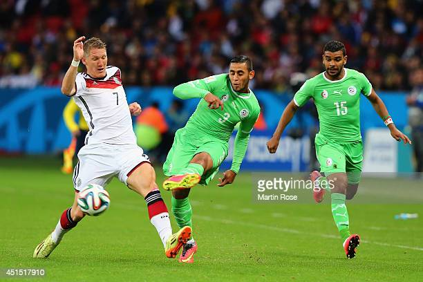 Bastian Schweinsteiger of Germany and Faouzi Ghoulam compete for the ball as El Arbi Hillel Soudani of Algeria looks on lduring the 2014 FIFA World...