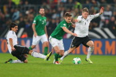 Bastian Schweinsteiger of Germany and his team mate Sami Khedira battle for the ball with Kevin Doyle of Ireland during the FIFA 2014 World Cup...
