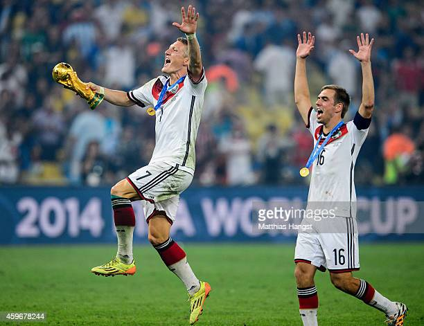 Bastian Schweinsteiger of Germany and Philipp Lahm of Germany celebrate with the World Cup trophy after defeating Argentina 10 in extra time during...