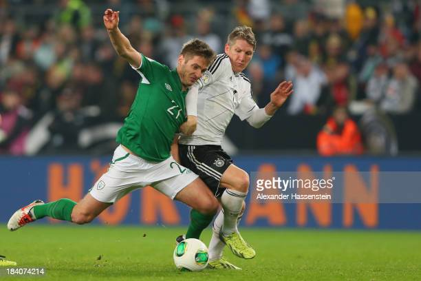 Bastian Schweinsteiger of Germany battles for the ball with Kevin Doyle of Ireland during the FIFA 2014 World Cup Qualifier Group C match between...
