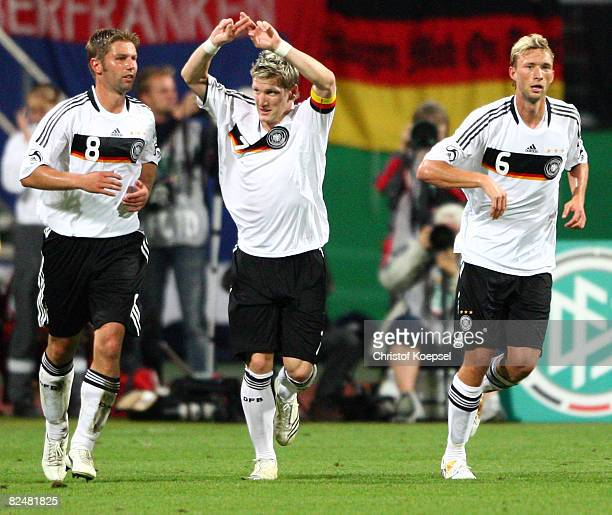 Bastian Schweinsteiger of Germany celebrates the first goal with Thomas Hitzlsperger and Simon Rolfes during the international friendly match between...