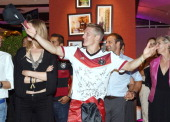 Bastian Schweinsteiger of Germany girlfriend Sarah Brandner and assistant coach Hansi Flick celebrate with teammates at a party after winning the...