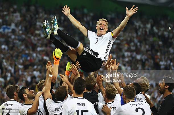 Bastian Schweinsteiger of Germany is thrown in to the air by team mates after his last international match during the International Friendly match...