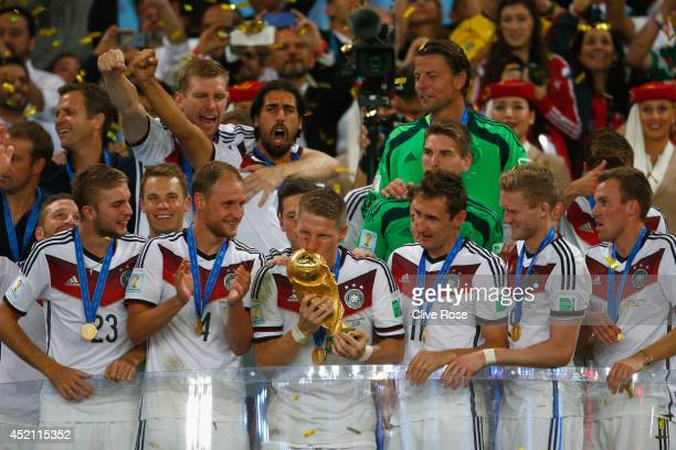 Bastian Schweinsteiger of Germany kisses the World Cup trophy with teammates after defeating Argentina 10 in extra time during the 2014 FIFA World...