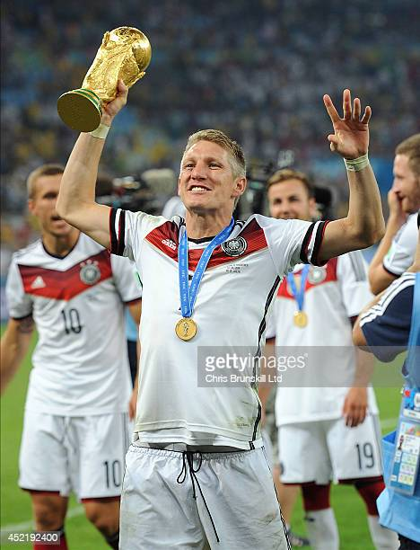 Bastian Schweinsteiger of Germany lifts the trophy following the 2014 World Cup Final match between Germany and Argentina at Maracana Stadium on July...
