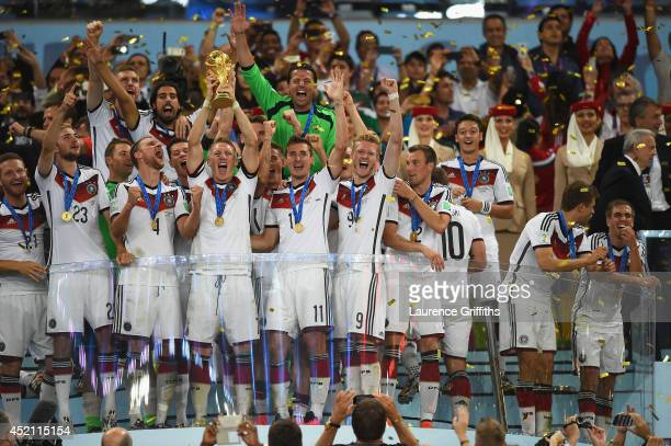 Bastian Schweinsteiger of Germany lifts the World Cup trophy and celebrates with teammates after defeating Argentina 10 in extra time during the 2014...