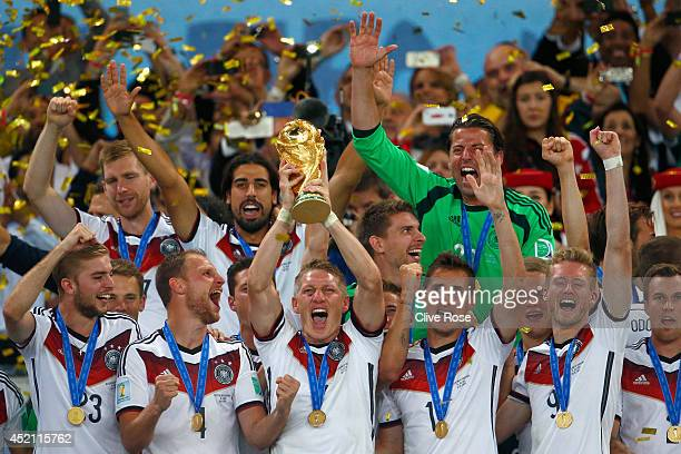 Bastian Schweinsteiger of Germany lifts the World Cup trophy with teammates after defeating Argentina 10 in extra time during the 2014 FIFA World Cup...