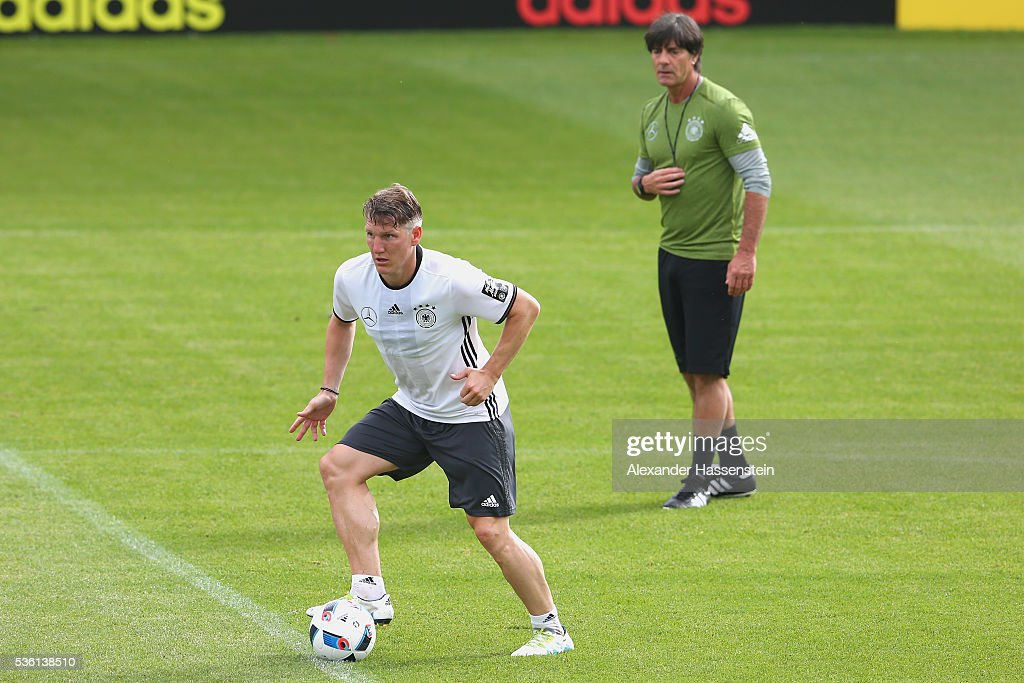 <a gi-track='captionPersonalityLinkClicked' href=/galleries/search?phrase=Bastian+Schweinsteiger&family=editorial&specificpeople=203122 ng-click='$event.stopPropagation()'>Bastian Schweinsteiger</a> of Germany plays the ball next to <a gi-track='captionPersonalityLinkClicked' href=/galleries/search?phrase=Joachim+Loew&family=editorial&specificpeople=215315 ng-click='$event.stopPropagation()'>Joachim Loew</a>, head coach of the German national team during a training session at Stadio communale on day 8 of the German national team trainings camp on May 31, 2016 in Ascona, Switzerland.