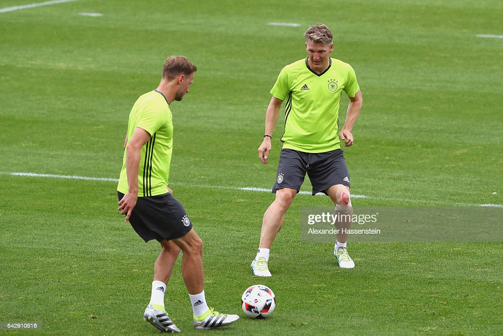 Bastian Schweinsteiger of Germany plays the ball with his team mate Benedikt Hoewedes (L) during a Germany training session ahead of their Euro 2016 round of 16 match against Slovakia at Ermitage Evian on June 25, 2016 in Evian-les-Bains, France.