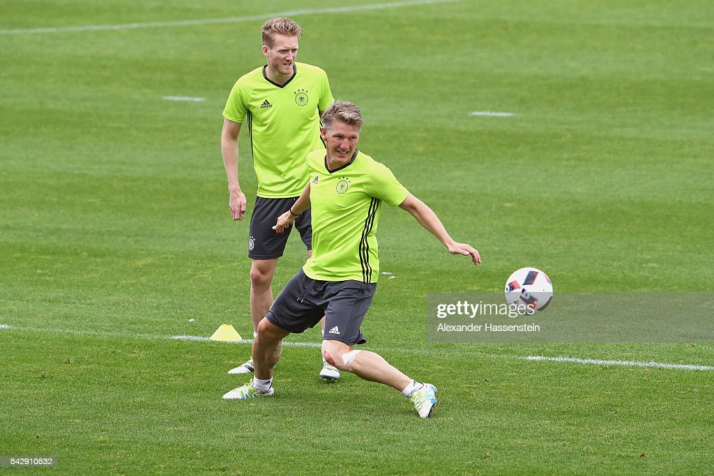 Bastian Schweinsteiger of Germany plays the ball with his team mate Andre Schuerrle (L) during a Germany training session ahead of their Euro 2016 round of 16 match against Slovakia at Ermitage Evian on June 25, 2016 in Evian-les-Bains, France.