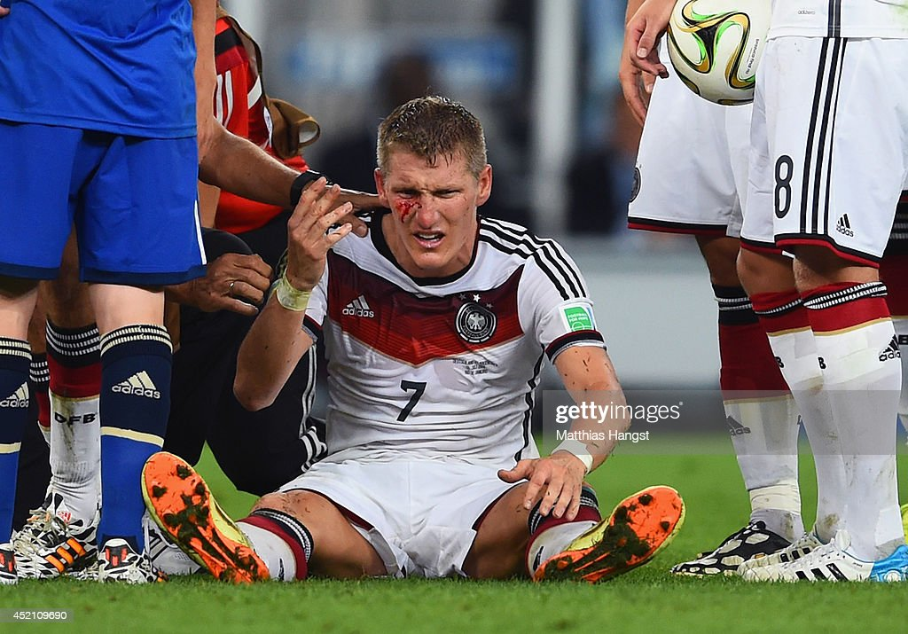 <a gi-track='captionPersonalityLinkClicked' href=/galleries/search?phrase=Bastian+Schweinsteiger&family=editorial&specificpeople=203122 ng-click='$event.stopPropagation()'>Bastian Schweinsteiger</a> of Germany receives treatment after a collision during the 2014 FIFA World Cup Brazil Final match between Germany and Argentina at Maracana on July 13, 2014 in Rio de Janeiro, Brazil.
