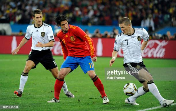 Bastian Schweinsteiger of Germany watched by Joan Capdevila of Spain during the 2010 FIFA World Cup South Africa Semi Final match between Germany and...