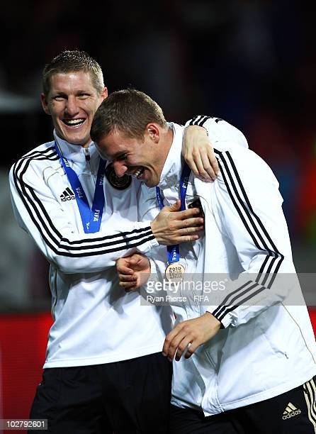 Bastian Schweinsteiger of Germany with team mate Lukas Podolski celebrate with their bronze medals for coming third place during the 2010 FIFA World...