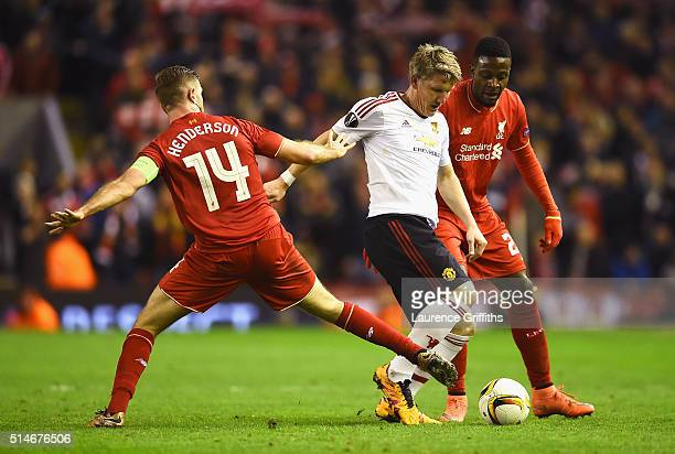 Bastian Schweinsteiger of Manchester United takes on Jordan Henderson and Divock Origi of Liverpool during the UEFA Europa League Round of 16 first...