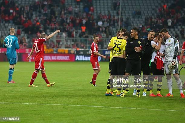 Bastian Schweinsteiger of Muenchen and his team mates Lukas Raeder and Philipp Lahm walk over the field whilst Roman Weidenfeller of Dortmund...