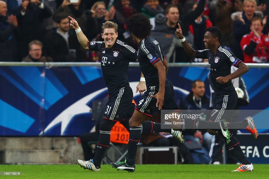Bastian Schweinsteiger of Muenchen celebrates his team's first goal with team mates Dante and David Alaba (L-R) during the UEFA Champions League group F match between FC Bayern Muenchen and LOSC Lille at Allianz Arena on November 7, 2012 in Munich, Germany.