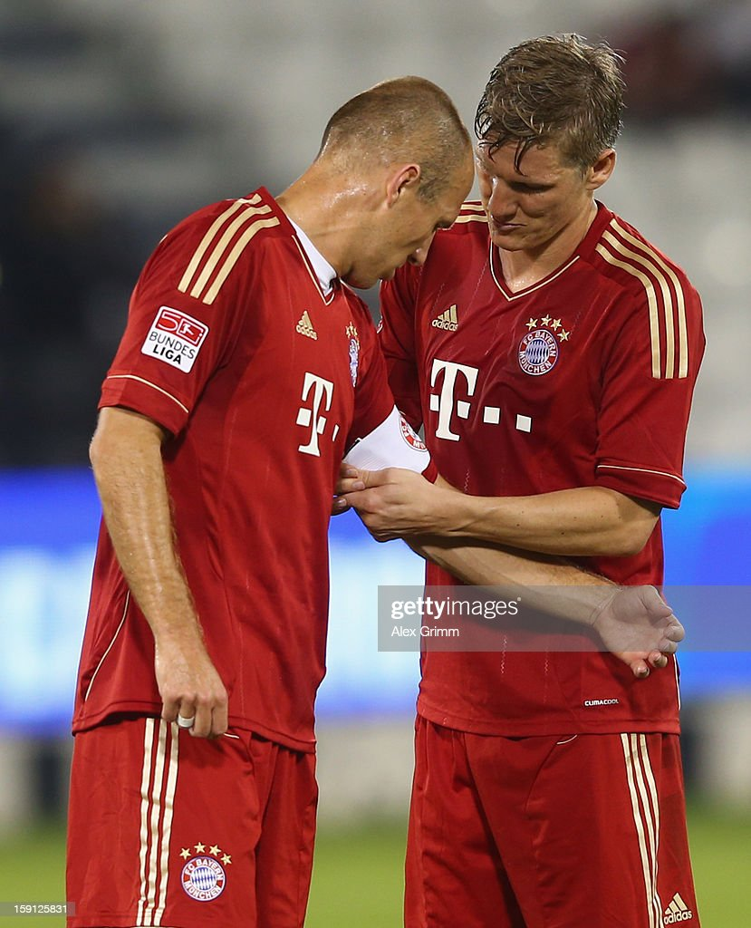 Bastian Schweinsteiger (R) of Muenchen hands over the captain's armband to Arjen Robben during the friendly match between Bayern Muenchen and FC Schalke 04 at Jassim Bin Hamad Stadium on January 8, 2013 in Doha, Qatar.