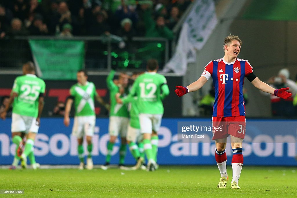 Bastian Schweinsteiger of Muenchen reacts as Kevin de Bruyne of Wolfsburg celebrates his team's third goal with team mates during the Bundesliga match between VfL Wolfsburg and FC Bayern Muenchen at Volkswagen Arena on January 30, 2015 in Wolfsburg, Germany.