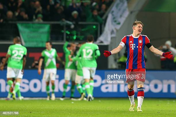 Bastian Schweinsteiger of Muenchen reacts as Kevin de Bruyne of Wolfsburg celebrates his team's third goal with team mates during the Bundesliga...