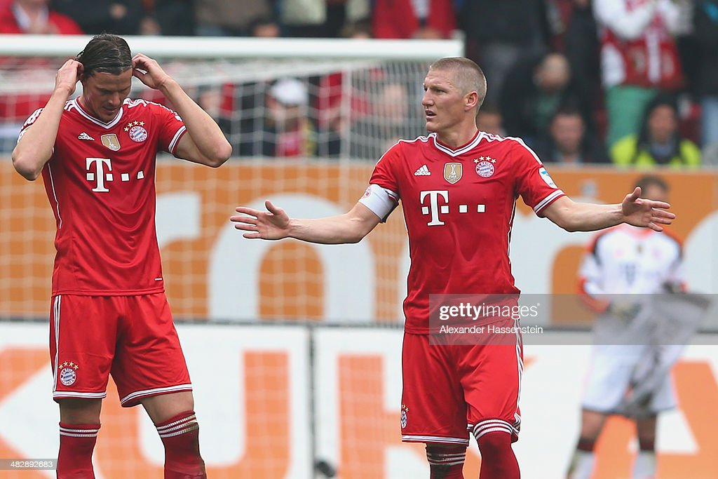<a gi-track='captionPersonalityLinkClicked' href=/galleries/search?phrase=Bastian+Schweinsteiger&family=editorial&specificpeople=203122 ng-click='$event.stopPropagation()'>Bastian Schweinsteiger</a> (R) of Muenchen reacts with his team mate <a gi-track='captionPersonalityLinkClicked' href=/galleries/search?phrase=Daniel+van+Buyten&family=editorial&specificpeople=213252 ng-click='$event.stopPropagation()'>Daniel van Buyten</a> after receiving the first goal during the Bundesliga match between FC Augsburg and FC Bayern Muenchen at SGL Arena on April 5, 2014 in Augsburg, Germany.