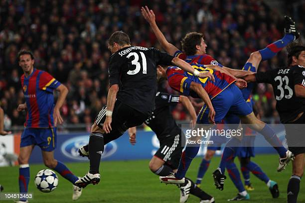Bastian Schweinsteiger of Muenchen scores his team's second goal against Behrang Safari and Valentin Stocker of Basel during the UEFA Champions...