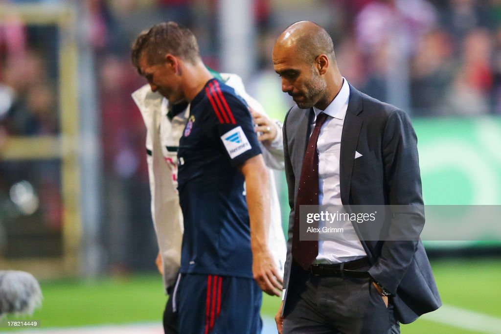 <a gi-track='captionPersonalityLinkClicked' href=/galleries/search?phrase=Bastian+Schweinsteiger&family=editorial&specificpeople=203122 ng-click='$event.stopPropagation()'>Bastian Schweinsteiger</a> (back) of Muenchen walks past head coach Pep Guardiola after being substituted during the Bundesliga match between SC Freiburg and FC Bayern Muenchen at MAGE SOLAR Stadium on August 27, 2013 in Freiburg im Breisgau, Germany.