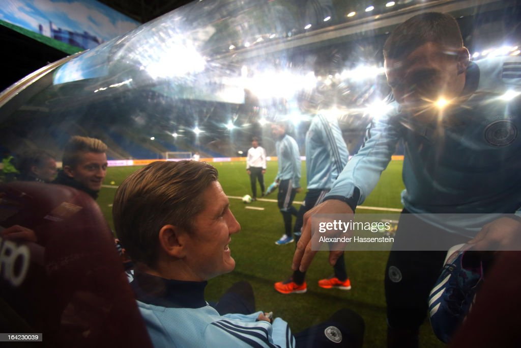 Bastian Schweinsteiger (L) of the German national football team jokes with his team mate Lukas Podolski (R) during a training session at Astana arena on March 21, 2013 in Astana, Kazakhstan.