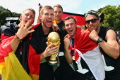 Bastian Schweinsteiger Per Mertesacker Manuel Neuer Kevin Grosskreutz and Lukas Podolski celebrate on stage at the German team victory ceremony on...