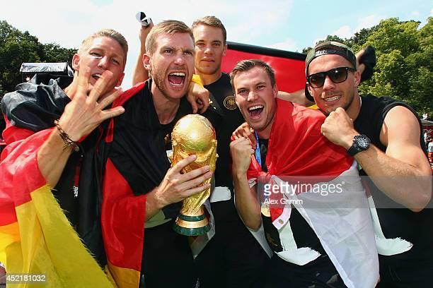 Bastian Schweinsteiger Per Mertesacker Manuel Neuer Kevin Grosskreutz and Lukas Podolski celebrate on stage at the German team victory ceremony on...