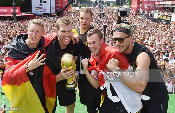Bastian Schweinsteiger Per Mertesacker Torwart Manuel Neuer Kevin Grosskreutz and Lukas Podolski celebrates on stage at the German team victory...