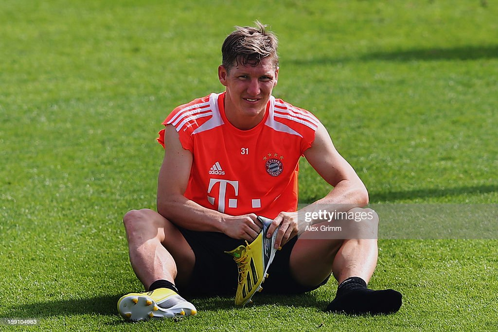 Bastian Schweinsteiger pulls off his boots after a Bayern Muenchen training session at the ASPIRE Academy for Sports Excellence on January 8, 2013 in Doha, Qatar.