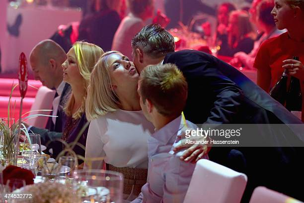 Bastian Schweinsteiger talks to his team mate Philipp Lahm and his wife Claudia Lahm during the FC Bayern Muenchen Bundesliga Champions Dinner at...
