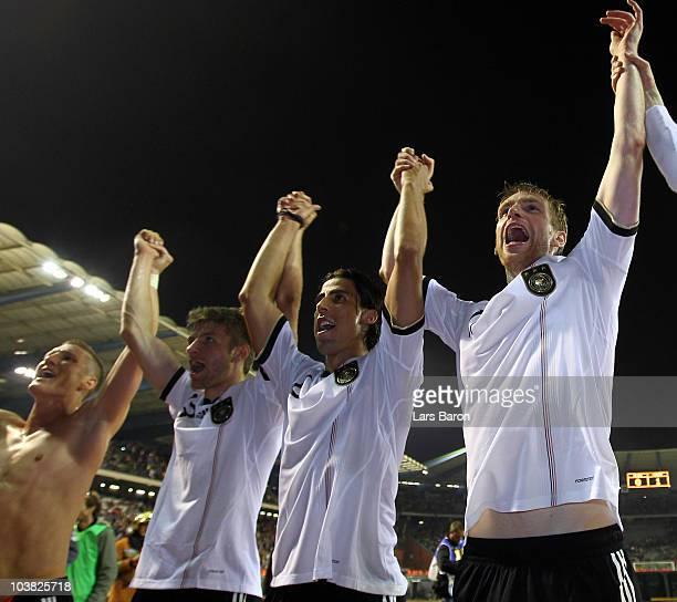 Bastian Schweinsteiger Thomas Mueller Sami Khedira and Per Mertesacker of Germany celebrate after winning the EURO 2012 Group A Qualifier match...