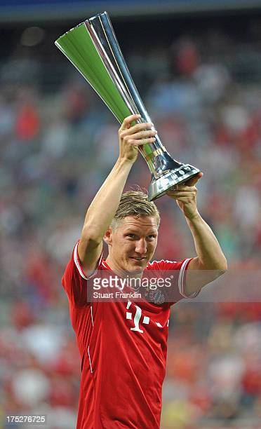 Bastian Schweinstieger of Muenchen holds the winners trophy after the Audi cup 2013 final between FC Bayern Muenchen and Manchester City at Allianz...