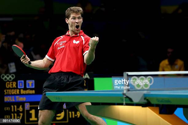 Bastian Steger of Germany celebrates winning the doubles match during the Men's Team Bronze Medal match between Korea and Germany at the Rio Centro...