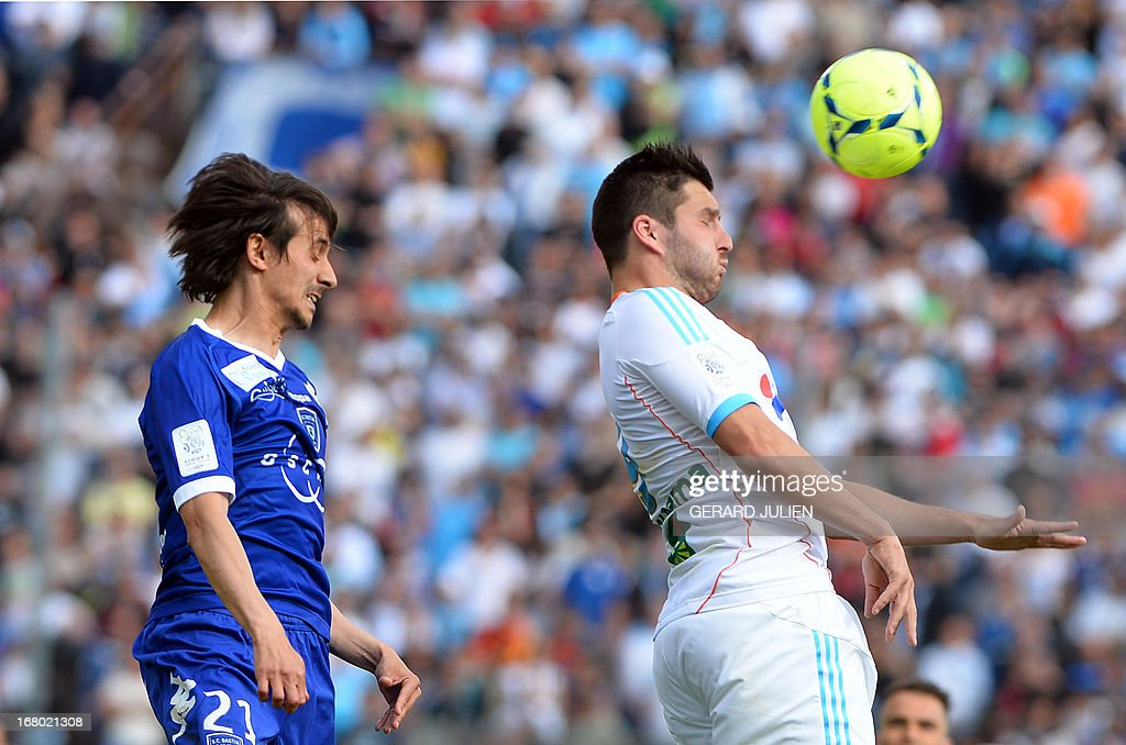 Bastia's Algerian defender Fethi Harek jumps for the ball with Marseille's French midfielder AndrePierre Gignac during the French L1 football match...