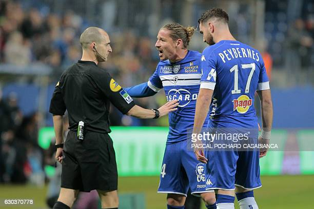 Bastia's Algerian midfielder Mehdi Mostefa and Bastia's French defender Mathieu Peybernes argue with main referee Benoit Millot during the French L1...