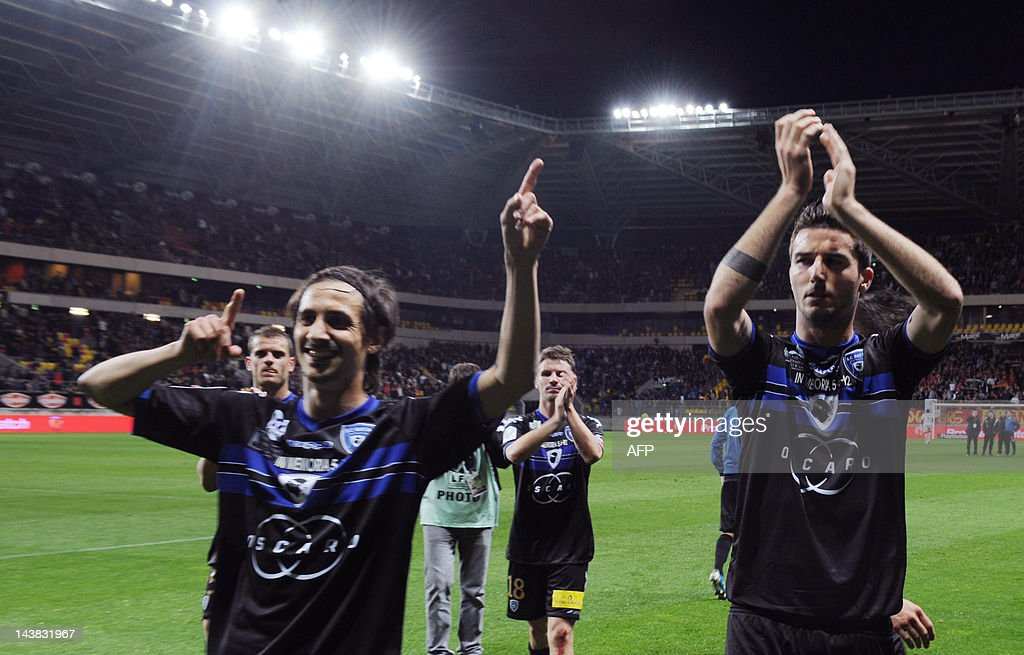 Bastia's French defenders Fethi Harek and Matthieu Sans cheer their supporters at the end of the French L2 football match Le Mans vs. Bastia on May 4, 2012 at the Le Mans Stadium in Le Mans, western France. Bastia won 3-0. Bastia returned to Ligue 1 after a seven year absence on May 1, 2012, as a 3-0 win over Metz assured them not only of promotion but also they would finish as champions. AFP PHOTO / JEAN FRANCOIS MONIER