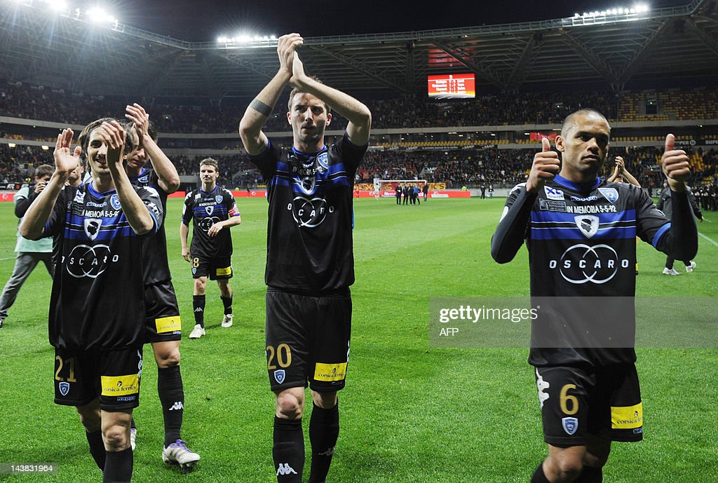Bastia's French defenders Fethi Harek, Matthieu Sans and Gael Angoula cheer theirs supporters at the end of the French L2 football match Le Mans vs. Bastia on May 4, 2012 at the Le Mans Stadium in Le Mans, western France. Bastia won 3-0. Bastia returned to Ligue 1 after a seven year absence on May 1, 2012, as a 3-0 win over Metz assured them not only of promotion but also they would finish as champions. AFP PHOTO / JEAN FRANCOIS MONIER