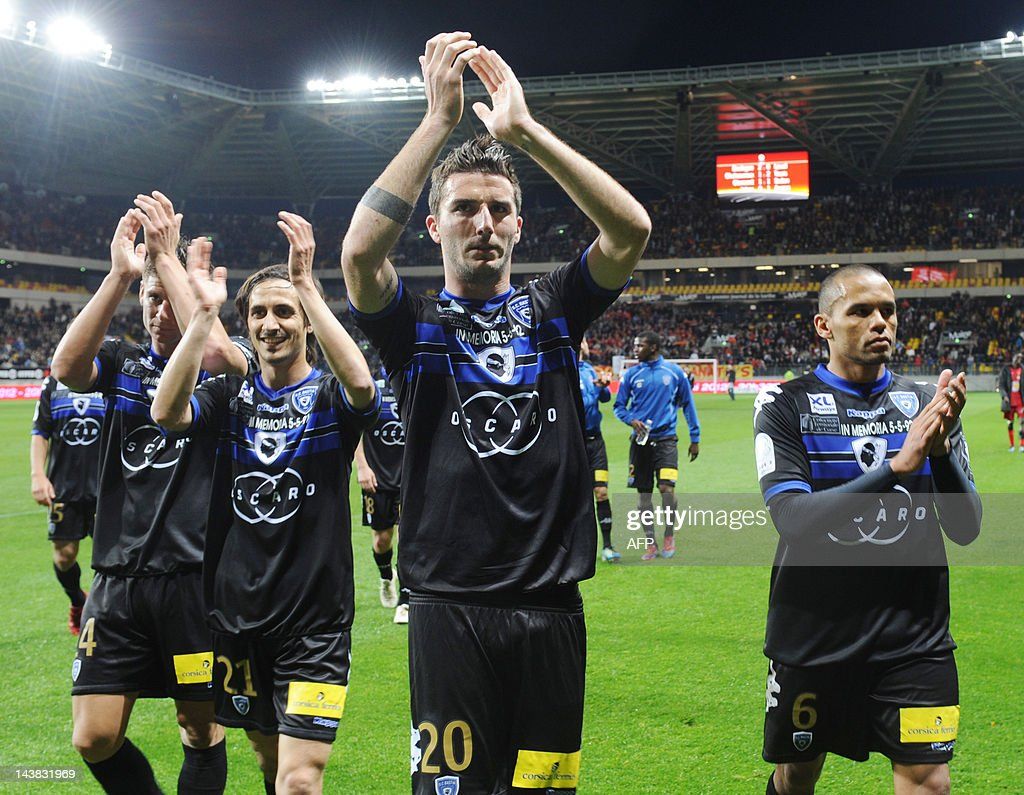 Bastia's French defenders Jeremy Choplin, Fethi Harek, Matthieu Sans and Gael Angoula cheer theirs supporters at the end of the French L2 football match Le Mans vs. Bastia on May 4, 2012 at the Le Mans Stadium in Le Mans, western France. Bastia won 3-0. Bastia returned to Ligue 1 after a seven year absence on May 1, 2012, as a 3-0 win over Metz assured them not only of promotion but also they would finish as champions. AFP PHOTO / JEAN FRANCOIS MONIER