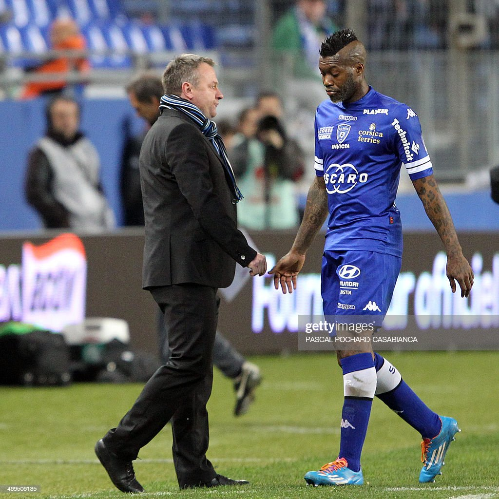 Bastia's French forward Djibril Cisse (R) looks dejected as he walks past Bastia's head coach Frederic Hantz while leaving the pitch during the French L1 football match Bastia (SCB) against Monaco in the Armand Cesari stadium in Bastia, Corsica, on February 15 , 2014. Monaco defeated Bastia 2-0.