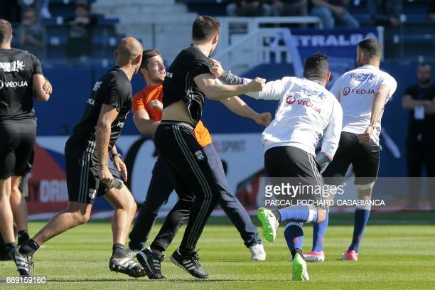 A Bastia's supporter fights with Lyon's player during their the warm up prior to the French L1 Football match between Bastia and Lyon on April 16 at...