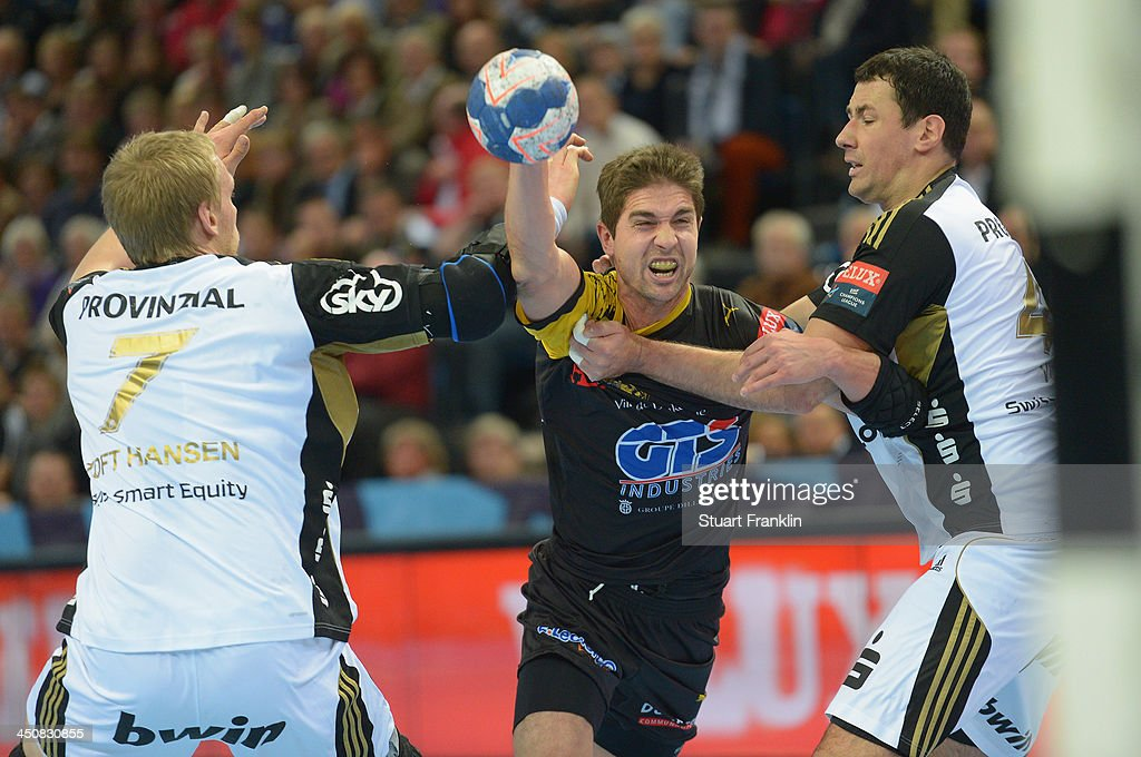 Bastien Lamon of Dunkerque challenges for the ball with Rene Toft Hansen and Marko Vujin of Kiel during the Velux EHF Champions League handball match between THW Kiel and US Dunkerque at the Sparkasse arena on November 20, 2013 in Kiel, Germany.